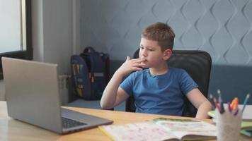 porträtt av en ung pojke som undervisar online på distans med bärbar dator och internet via videochatt. distansutbildning hemma. foto