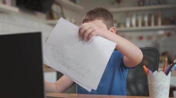 skolbarn visar anteckningsbok till bärbar datorskärm medan han studerar online hemma. onlineundervisning och distansundervisning för barn. ung pojke gör läxor via internet. foto