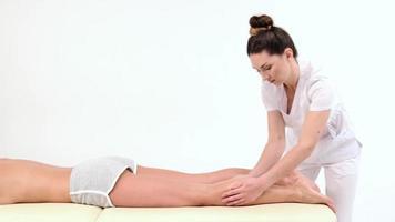 kvinnlig massör gör benmassage. avkopplande massage på ljus bakgrund foto
