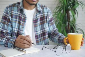 ung man som skriver på anteckningsblock medan han håller en kaffemugg foto