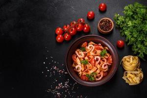 fettuccinapasta med räkor, körsbärstomater, sås, kryddor och örter foto