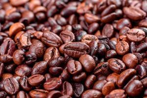 korn av färskt rostat kaffe närbild mot en mörk bakgrund foto