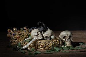 stilleben skalle och skorpion med skatt guld pirat smycken foto