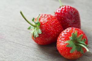 färska jordgubbar på träbord foto
