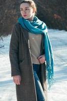 charmig tjej, blå halsduk och jeans, brun kappa, mode, vinterdag foto