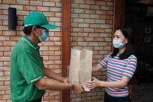 leveransman med ansiktsmask ger paket till en asiatisk kvinna. foto