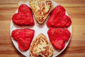 röda hjärtformade pannkakor gjorda med kärlek till alla hjärtans dag foto