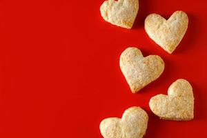 hjärtformade sockerkakor på röd bakgrund foto