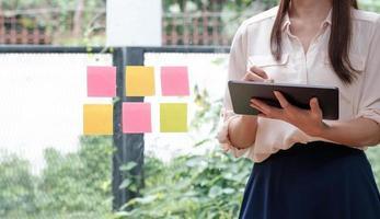 närbild affärskvinna med hjälp av miniräknare och bärbar dator foto