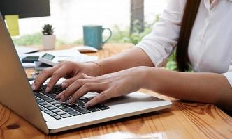 närbild av en asiatisk affärskvinna som arbetar och skriver på en bärbar dator foto