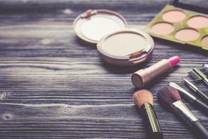 ovanifrån en samling kosmetisk smink och anteckningsbok på träbord foto