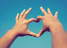man händer form från kärlek himmel bakgrund foto