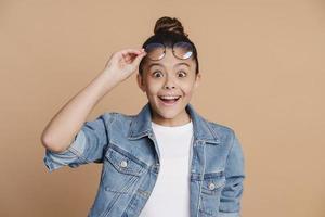 förvånad, söt tonårsflicka höjde glasögonen. förvånad liten tjej foto