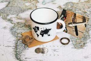 vit mugg med en karta över världen på bakgrunden av världskartan foto