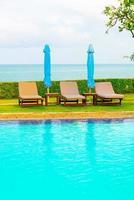 stol pool och paraply runt poolen med havet havet bakgrund foto