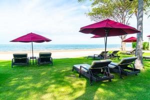 strandstol och paraply med havets havsbakgrund foto