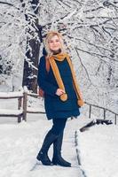 vacker ung flicka i en vinterpark promenader i vinterskogen foto