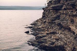 textur av en stenig strand nära vattnet. stenhög bakgrund foto