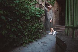 flicka i hatt öppnar en brevlåda i bakgrunden av det gamla huset foto