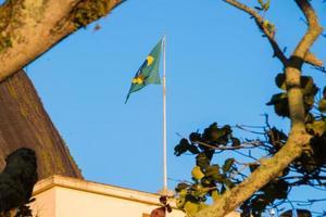 Brasiliens flagga utomhus med en vacker blå himmel i bakgrunden foto