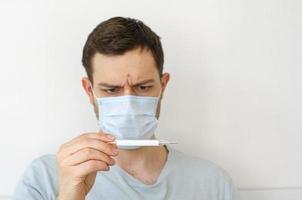 en man mäter temperaturen. värme. i masken. foto