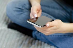 en ung flicka använder sin mobiltelefon. kommunikation på distans. foto