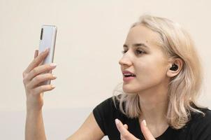 flicka kommunicerar med videosamtal. trådlösa hörlurar. foto