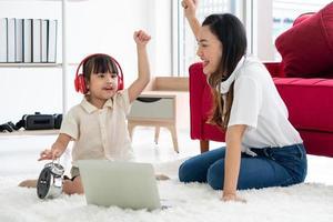 asiatisk mamma med att lära barn att studera från datorn hemma foto