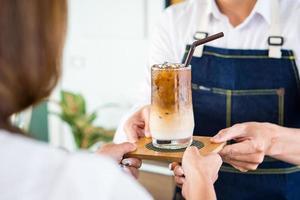 ung barista förbereder isad latte för att betjäna kunden i caféet foto