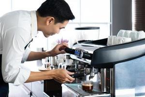 ung asiatisk barista brygger kaffe från kaffebryggarmaskin i café foto