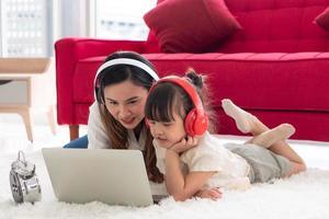 asiatisk mamma som lär dotter att studera från datorprogram hemma foto