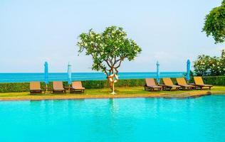 stol pool eller säng pool och paraply runt poolen med havsbakgrund - semester och semester koncept foto
