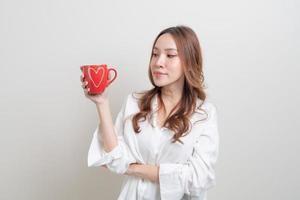 porträtt vacker asiatisk kvinna som håller kaffekopp eller mugg på vit bakgrund foto