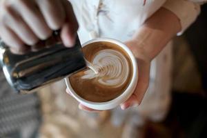 barista som skapar latte art kaffe. foto