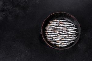 flera fisksaltade ansjovis på ett mörkt betongbord foto
