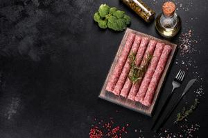 färska råa fläskkorvar med kryddor på en skärbräda i trä foto