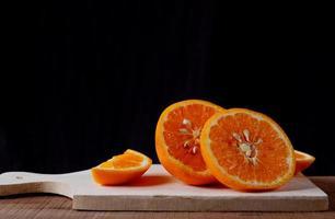 apelsinskivor på träskärbräda på svart bakgrund foto