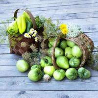 grönsaker i en korg och en bukett vilda blommor på bakgrunden foto