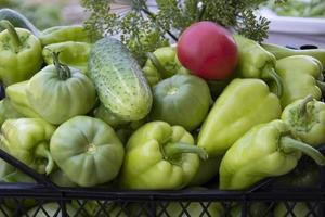 grönsaker i en svart låda och en bukett vildblommor foto