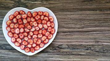 de skivade jordgubbarna finns i en hjärtformad tallrik foto