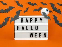 ljuslåda med glad halloween -fras med fladdermöss och dekoration för ögongloben foto