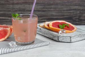 cocktail med grapefrukt på en ljus bakgrund med en myntakvist foto