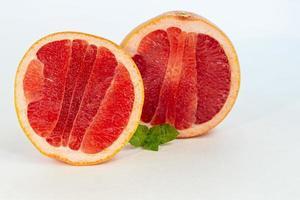 grapefrukt på en vit tallrik med en myntakvist. isolera. foto