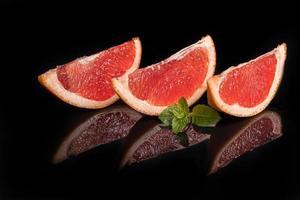 skivor grapefrukt på en mörk bakgrund med en myntakvist. foto