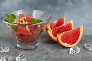 sommarsallad med grapefrukt på en ljus bakgrund med örter. foto