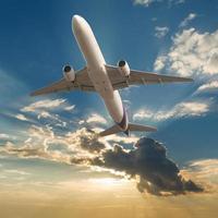 kommersiellt flygplan som flyger med moln och solstrålar bakgrund foto