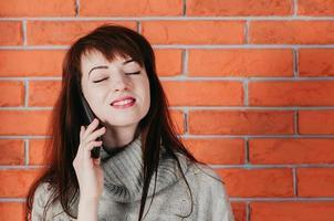 en vacker tjej som pratar med mobiltelefon, ler, stängda ögon, tegelvägg foto