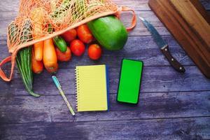 färska grönsaker, skärbräda, anteckningsblock och smart telefon på bordet foto