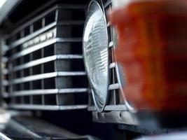 strålkastare och galler närbild av en gammal vacker bil. foto