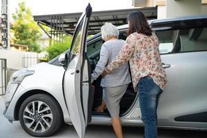 hjälp och stöd asiatisk senior kvinna patient förbereda sig komma till sin bil. foto